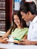 Bibliothecaris And Schoolgirl Looking samen bij Boek royalty-vrije stock afbeeldingen