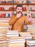 Bibliothecarisconcept De mens op nadenkend gezicht bevindt zich tussen stapels van boeken, terwijl zandloper, boekenrekken houdt stock fotografie