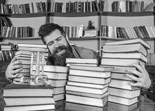 Bibliothecarisconcept Mens op gelukkig gezicht tussen stapels van boeken, terwijl het bestuderen in bibliotheek, boekenrekken op  stock foto's