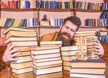 Bibliothecarisconcept Mens op gelukkig gezicht tussen stapels van boeken, terwijl het bestuderen in bibliotheek, boekenrekken op  royalty-vrije stock afbeeldingen