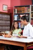 Bibliothecarisleraar And Schoolgirl Looking bij elk royalty-vrije stock foto's