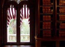 Bibliothek in einer Dunkelkammer mit antikem Fenster stockbilder