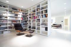 Bibliothek innerhalb des teuren, modernen Wohnsitzes Lizenzfreie Stockfotos