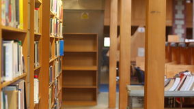 Bibliothekar, der Laufkatze durch die zurückgehenden Bücher der Bibliothek drückt stock footage