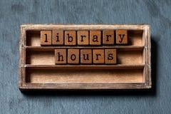 Bibliotheksstunden conept Weinleseblöcke mit Buchstaben, gealterte Holzkiste Grauer Steinhintergrund, Makro, Weichzeichnung Stockbild