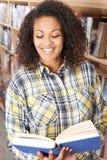 Bibliothèque de Reading Book In d'étudiante Image stock