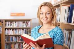 Bibliothèque de Reading Book In d'étudiante Photographie stock libre de droits