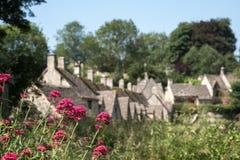 Bibury俏丽的村庄在Cotswolds英国的,用红色拔地响在前景和阿灵顿行村庄开花在后面 免版税库存照片