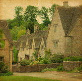 Bibury in spring. Traditional Cotswold cottages in England, UK. Photo in retro style. Paper texture Stock Image