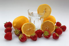 Bicchiere d'acqua con i limoni e le fragole su fondo bianco Fotografia Stock Libera da Diritti