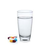 Bicchiere d'acqua con la capsula della pillola Fotografie Stock