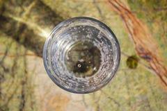 Bicchiere d'acqua con le bolle sulla tavola immagini stock libere da diritti