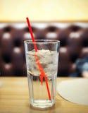 Bicchiere d'acqua con paglia rossa sulla tavola di legno immagine stock libera da diritti