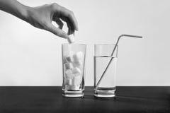 Bicchiere d'acqua contro zucchero, malattia del diabete, dipendenza dolce Fotografie Stock