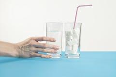 Bicchiere d'acqua contro zucchero, malattia del diabete, dipendenza dolce, mano Immagine Stock Libera da Diritti