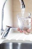 Bicchiere d'acqua di riempimento a disposizione dal rubinetto della cucina Fotografie Stock