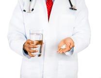 Bicchiere d'acqua di tenuta professionale di sanità in una mano ed in pillole bianche Fotografia Stock
