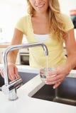 Bicchiere d'acqua di versamento della donna dal rubinetto in cucina Fotografia Stock