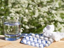 Bicchiere d'acqua e delle pillole, fazzoletto sulla tavola su nazionale verde Immagine Stock