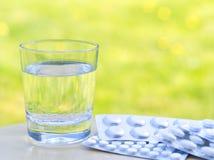 Bicchiere d'acqua e delle pillole sulla tavola sul fondo verde della natura Allergico ai fiori ed al polline Spazio vuoto, defocu Immagine Stock