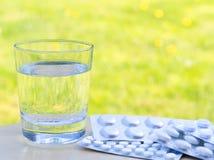 Bicchiere d'acqua e delle pillole sulla tavola sul fondo verde della natura Allergico ai fiori ed al polline Spazio vuoto Immagini Stock