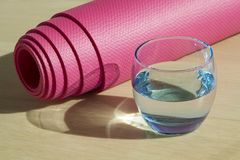 Bicchiere d'acqua e stuoia blu di forma fisica fotografie stock libere da diritti