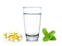 Bicchiere d'acqua ed olio di pesce su fondo bianco Fotografia Stock