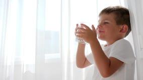 Bicchiere d'acqua in mani del ragazzino che beve l'acqua minerale sulle tende di bianco del fondo video d archivio