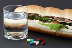 Bicchiere d'acqua, pillole e due hot dog con i vari ingredienti Fotografia Stock