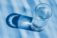 Bicchiere d'acqua su un fondo blu Fotografie Stock