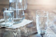 Bicchiere d'acqua su una tavola di legno Fotografie Stock Libere da Diritti