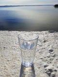 Bicchiere d'acqua sul beton con la vista del mare immagine stock
