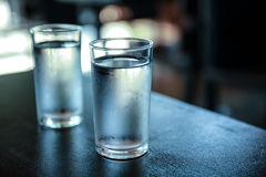 Bicchiere d'acqua sulla tavola nera Immagine Stock