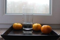 Bicchiere d'acqua trasparente con i mandarini sul vassoio nero Immagini Stock Libere da Diritti