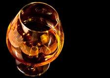 Bicchiere da brandy di brandy in vetro tipico elegante del cognac su fondo nero Fotografia Stock