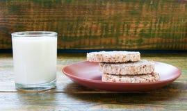 Bicchiere di latte con il pane croccante sul piatto dell'argilla fotografia stock