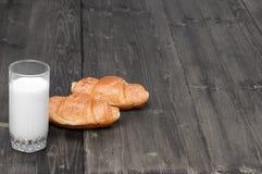 Bicchiere di latte con le paia dei croissant su un vecchio fondo di legno rustico grigio con lo spazio della copia per il vostro  Fotografia Stock
