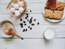 bicchiere di latte, dolce casalingo, uova, cinorrodi e fiocchi di avena in un piatto sulla tavola bianca Fotografie Stock Libere da Diritti