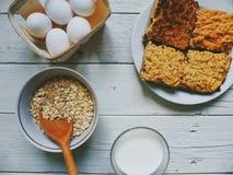 bicchiere di latte, dolce casalingo, uova e farina d'avena in una ciotola su una tavola bianca Fotografia Stock