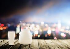 Bicchiere di latte e città fotografia stock