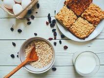 bicchiere di latte, un pezzo di dolce casalingo, uova e farina d'avena in una ciotola Fotografia Stock