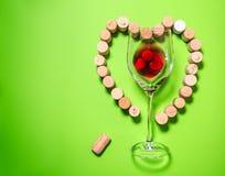 Bicchiere di vino con i tappi del sughero Immagini Stock