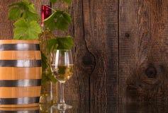 Bicchiere di vino con la bottiglia bianca del barilotto dietro i grapeleaves Immagine Stock Libera da Diritti