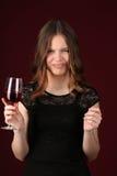 Bicchiere di vino della tenuta della ragazza dello smorfia Fine in su Priorità bassa rosso scuro Fotografia Stock Libera da Diritti