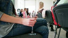 Bicchiere di vino della tenuta, jeans d'uso della donna che si siedono all'evento e che tengono vetro della bevanda dell'alcool archivi video