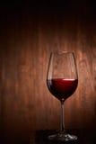 Bicchiere di vino fragile pieno a metà di vino rosso che sta su un fondo di legno Fotografie Stock