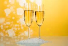 Bicchiere di vino meraviglioso due di champagne con le bolle di aria, vicino alla manciata di neve artificiale su giallo luminoso Fotografia Stock