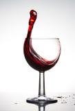 Bicchiere di vino puro con l'onda di vino rosso brillantemente su fondo bianco immagine stock