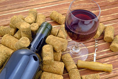 Bicchiere di vino su fondo della bottiglia e dei sugheri Fotografie Stock Libere da Diritti