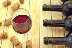 Bicchiere di vino su fondo delle bottiglie e dei sugheri Fotografia Stock